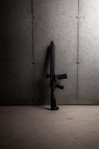 black rifle leaning on white wall