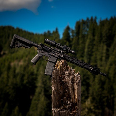 black assault rifle on brown wood