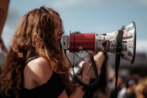 selective focus photography of woman wearing black cold-shoulder shirt using megaphone during daytime