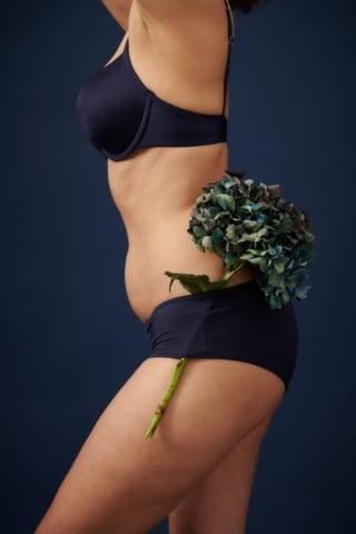 woman in black bikini holding bouquet of flowers