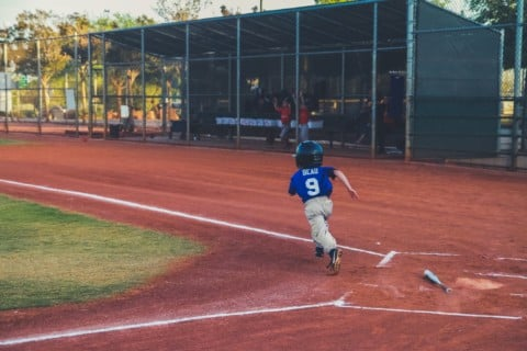 boy hit the ball running for the next base