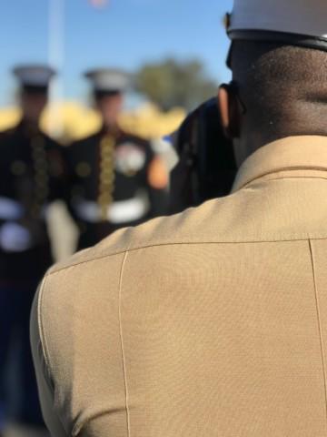 man in brown office uniform facing people in black officer uniform