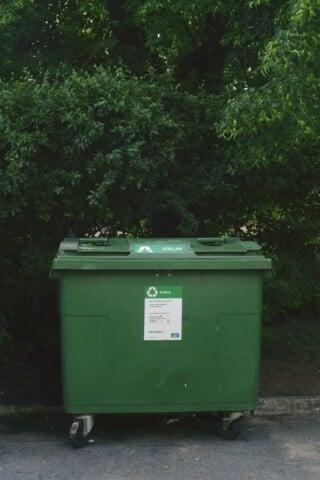 green trash bin near trees