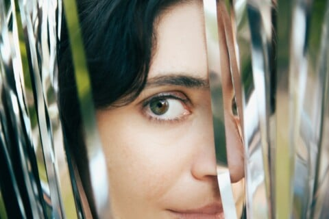 womans face with white and brown stripe curtain