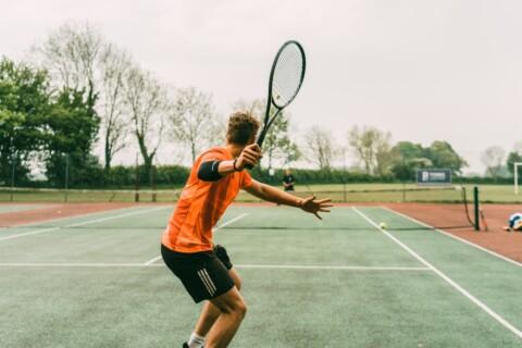 man in orange shirt and black shorts holding black and white tennis racket