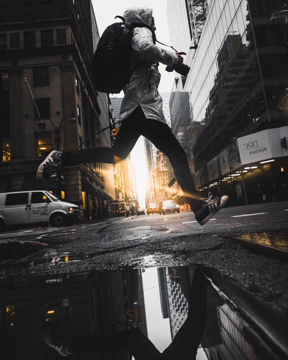person jumping above puddle of water