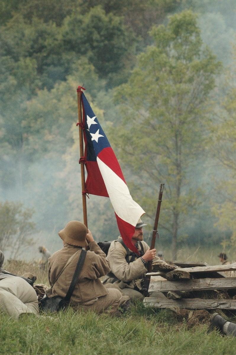 soldiers waving flag in battlefield